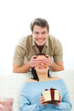 Man closing eye to girlfriend to present gift Royalty Free Stock Photo