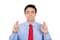 Man closing eyes and crossing fingers wishing and praying for miracle Stock Photo