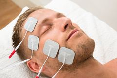 Man closing eyes with electrodes on face Stock Photo