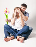 Man closing eyes of pregnant wife and giving her flower Royalty Free Stock Images