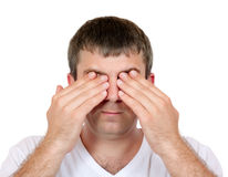 Man closing his eyes. Close-up portrait of a man closing his eyes with his hands on a white background studio royalty free stock photos