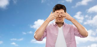 Man closing his eyes by hands over blue sky. Vision and people concept - man closing his eyes by hands over blue sky and clouds background stock photography