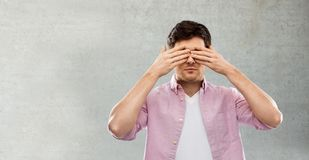 Man closing his eyes by hands over concrete wall. Vision and people concept - man closing his eyes by hands over grey background royalty free stock photo