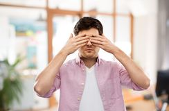 Man closing his eyes by hands over office room. Vision and people concept - man closing his eyes by hands over office room background royalty free stock image