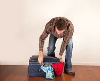 Man closing his overfull suitcase stock photo
