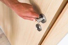 Man closing a light wood interior door Stock Photos
