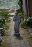 Man of the cloth in a garden. Statue of a priest on a garden walk Stock Photo