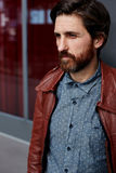 A man clothed his jacket and went to the balcony on a clear day. Portrait of fashionable hipster man dressed in pattern shirt and leather jacket standing indoors royalty free stock photography