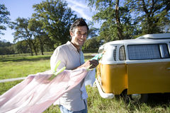 Man by clothes line by camper van in field, smiling, portrait Stock Image