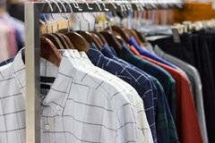 Man clothes multi color on hangers for sale. Man clothes multi color on hangers in shopping mall of  Thailand Stock Photos
