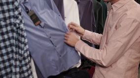 Man is in a clothes shop is examining garment on hanger, finding shirts stock video footage