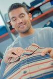 Man in clothes shop looking at shirt. Clothes Stock Photos
