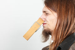 Man with clothespin on nose. Man with clothespin clip peg on his nose. Young long haired guy feeling unpleasant odor stink. Bad smell concept royalty free stock images