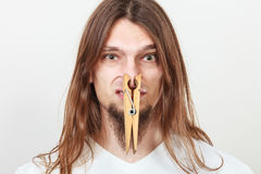 Man with clothespin on nose. Man with clothespin clip peg on his nose. Young long haired guy feeling unpleasant odor stink. Bad smell concept royalty free stock photography
