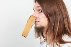 Man with clothespin on nose. Man with clothespin clip peg on his nose. Young long haired guy feeling unpleasant odor stink. Bad smell concept stock image