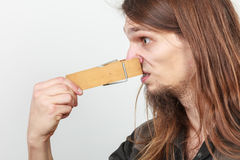 Man with clothespin on nose. Man with clothespin clip peg on his nose. Young long haired guy feeling unpleasant odor stink. Bad smell concept stock images