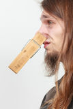 Man with clothespin on nose. Man with clothespin clip peg on his nose. Young long haired guy feeling unpleasant odor stink. Bad smell concept royalty free stock image