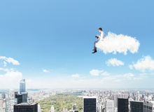 Man on a cloud reading a book Stock Images