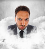 Man in the clouds with expression of indecision. Young businessman in the clouds with expression of indecision royalty free stock images