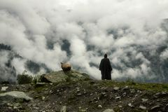 The man in the clouds. The man watching to the infinite of nature from the cliff royalty free stock photos