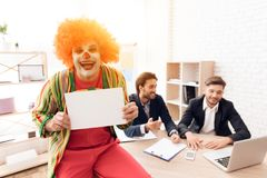 A man in a clown suit stands beside men in business suits, who sit at the desk. Stock Photos