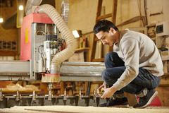 Man at the CNC machine. Tool with computer numerical control. Woodworking industry royalty free stock image