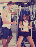 Man coach assisting woman in using pec deck. Well trained men coach assisting young pretty women in using pec deck gym machinery indoors Royalty Free Stock Image
