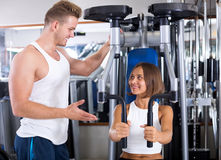 Man coach assisting woman in using pec deck. Well trained men coach assisting young women in using pec deck gym machinery indoors Stock Photos