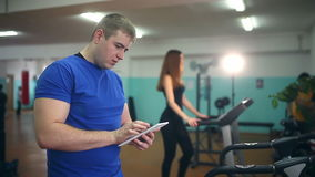Man coach in gym girl with the tablet on the treadmill fitness, healthy lifestyle, sport stock video