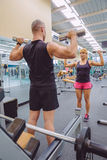 Man coach training to woman with dumbbells exercises. Man coach training to beautiful women with dumbbells exercises on fitness center. Personal trainer concept Stock Image