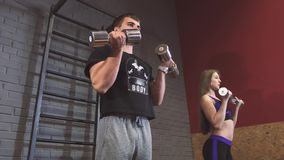 Man coach training women with dumbbells exercises on fitness center. Personal trainer for young and senior stock footage