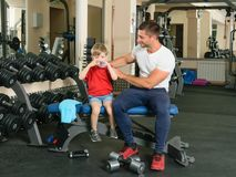 Man coached by boy. Pope shows little son how to lift weights in the gym Royalty Free Stock Photography