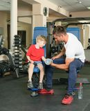 Man coached by boy. Pope shows little son how to lift weights in the gym Stock Image