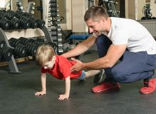 Man coached by boy. Pope shows little son how to lift weights in the gym Royalty Free Stock Photo