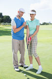Man coaching his partner on the putting green Stock Photo