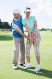 Man coaching his partner on the putting green Royalty Free Stock Images