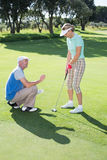 Man coaching his partner on the putting green Stock Images
