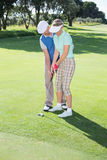 Man coaching his partner on the putting green Royalty Free Stock Image