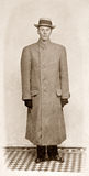 Man in Coat. Early 1920s antique photo of man in overcoat and hat.  Sepia-toned color file with noise added Stock Photos