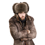 Man in the coat feel cold. Young bearded man in the coat and earflaps hat, feel cold, isolated on a white background stock image