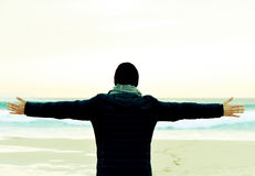 Man in coat with his arms in the air in front of the ocean. Closeup of a young caucasian man seen from behind wearing scarf, a knit cap and a coat with his arms Stock Photography