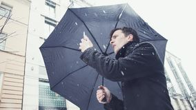 Man in coat and knitted scarf with umbrella under snowfall using smartphone. Young man with an umbrella under a snowfall using a smartphone. City alley on the stock footage