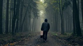 Man in coat with old suitcase in a foggy autumn forest