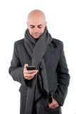 Man with coat and scarf using his smart phone. Royalty Free Stock Image