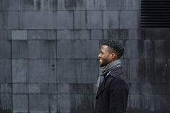 Man in coat. Side view of smiling man in black coat and grey scarf Stock Photo