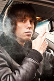 Man in coat smoking cigarette while sitting on passenger seat Stock Image