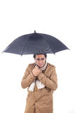 Man in the coat with umbrella freezes Stock Image