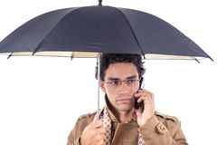 Man in the coat with an umbrella on the phone Royalty Free Stock Image