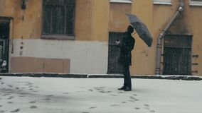 Man in coat with umbrella standing under snow holding plastic cup with coffee. Young man in gray coat with black umbrella standing under snowfall in the middle stock footage