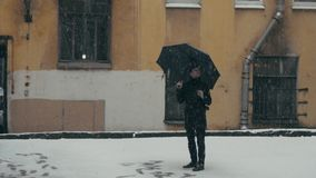 Man in coat with umbrella standing under snow holding plastic cup with hot drink. Lonely young man in gray coat with umbrella standing under snowfall in middle stock footage